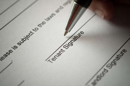 agency agreement: Rental agreement form with signing hand and pen.