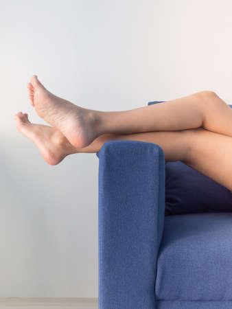 Long woman legs on sofa. Zdjęcie Seryjne