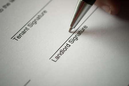 bienes raices: Forma del contrato de alquiler con la firma de la mano y la pluma.