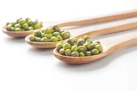 ejotes: Frijol mungo verdes en la cuchara de madera sobre fondo blanco. Foto de archivo