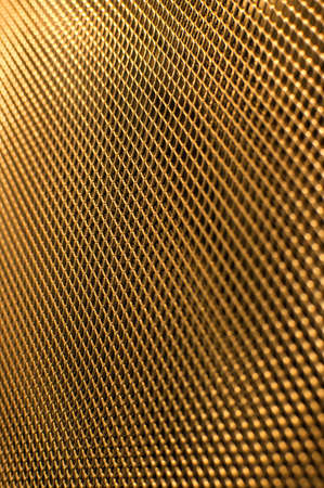 perforated: Perforated gold metal grate background.