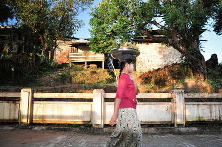 impoverished: Kyaikto, Myanmar -  October 22, 2015 .Local woman put the stuff on  head while walking to market .