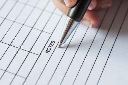 � writing: Manos femeninas con la pluma de escritura en papel con la lista de la tabla.
