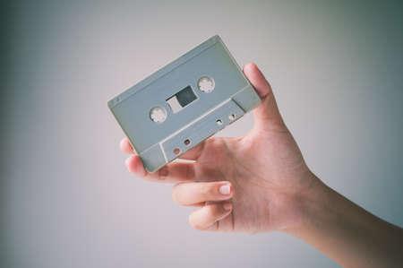 tape: Hand offer old retro cassette tape. Vintage image processed.