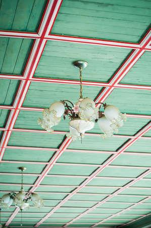 vintage chandelier: Vintage chandelier on green wood ciel background. Stock Photo