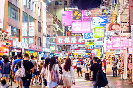 characterized: Hong Kong, China - October 03, 2015 : Many people in Mongkok street at night. Mongkok is characterized by a mixture of old and new multi-story buildings, with shops and restaurants at street level. Editorial