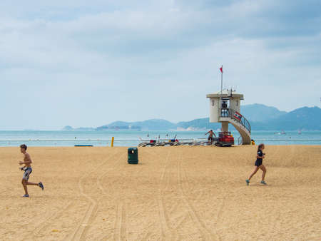 repulse: Hong Kong, China - October 03, 2015: People jogging at Repulse bay beach. Editorial