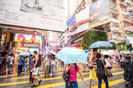 characterized: Hong Kong, China - October 03, 2015 : Many people in Mongkok street in rainy day. Mongkok is characterized by a mixture of old and new multi-story buildings, with shops and restaurants at street level.