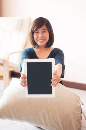 blank tablet: Young asian woman holding blank digital tablet, Focused on the tablet. Stock Photo