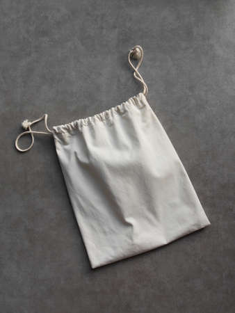 Cotton laundry bag on cement floor background