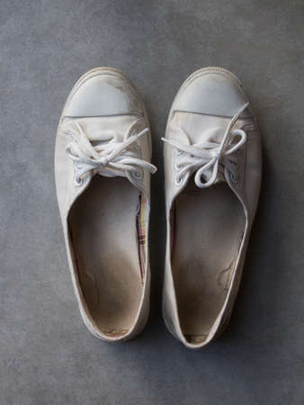 old shoes: Old white woman sneaker on cement floor background