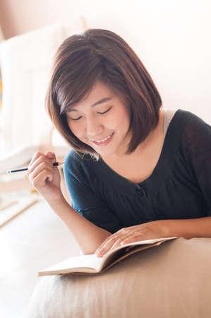 mujer en la cama: Joven mujer asi�tica escritura diario notas note en traje casual. Foto de archivo