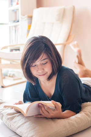 girl studying: Young asian woman reading book feeling relax in livingroom.