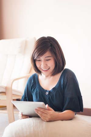 felling: Young asian woman holding digital tablet and felling wonderful. Stock Photo