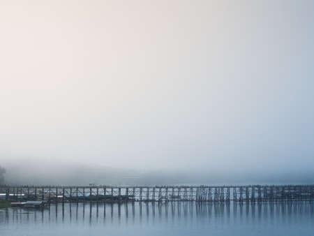 street life: Landscape of famous wood bridge (Mon Bridge) in misty morning at Sanklaburi, Thailand