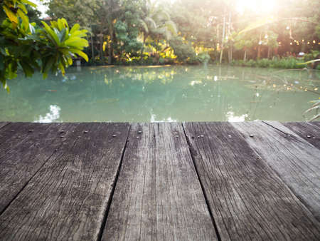 Old wood dock with garden pond on background. Stock fotó
