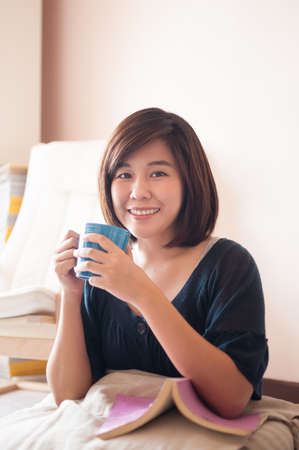 young asian: Young asian woman reading book and drinking fresh coffee