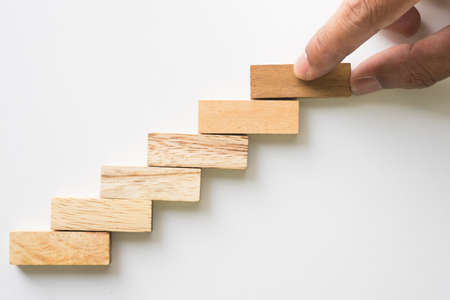 Hand aranging wood block stacking as step stair. Business concept for growth success process. Stockfoto