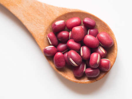 frijoles rojos en cuchara de madera sobre fondo blanco.