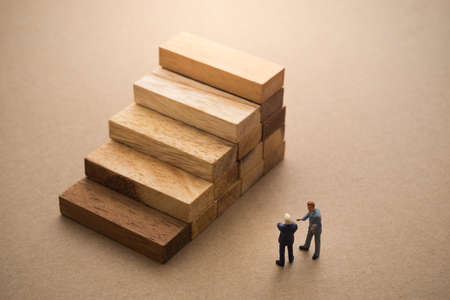 cardbox: Businessmen talking about wood block step, Successive business concept.