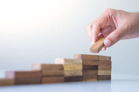 Hand aranging wood block stacking as step stair. Business concept for growth success process. 写真素材