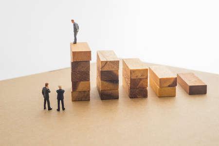 miniature: Businessmen talking about wood block step, Successive business concept.