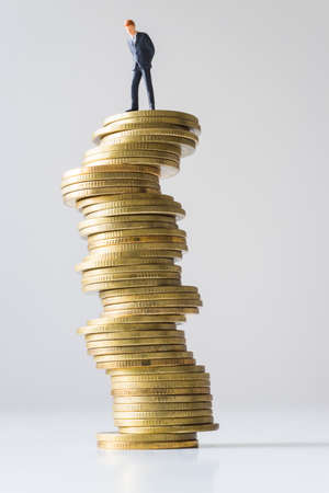 risky: Businessman standing on risky coin stack. Financial crisis concept.