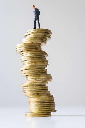 dangerous ideas: Businessman standing on risky coin stack. Financial crisis concept.