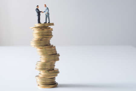 risky: Businessmen standing checking hands on risky coin stack. Financial crisis concept. Stock Photo