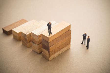 economia: Hombres de negocios hablando sobre el paso de bloque de madera, concepto de negocio sucesivos. Foto de archivo