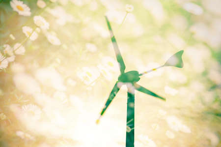 Wind turbines silhouette at sunset with flower field background, double exposure. Stock Photo