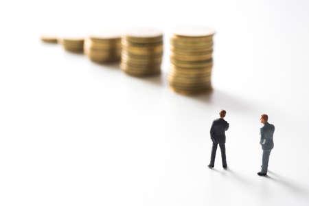 Geschäftsmann vor Münzen Stacks zu denken. Anlagekonzept. Standard-Bild