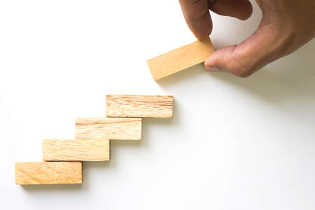success strategy: Hand aranging wood block stacking as step stair. Business concept for growth success process. Stock Photo