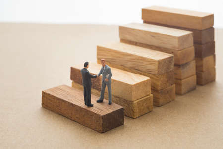 Businessmen checking hand on first step of wood stair, Successive business concept.