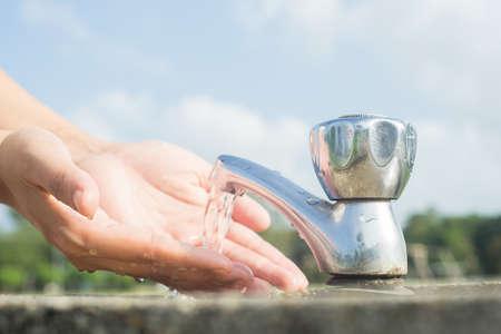 lavandose las manos: las manos se lavan en el grifo al aire libre Foto de archivo