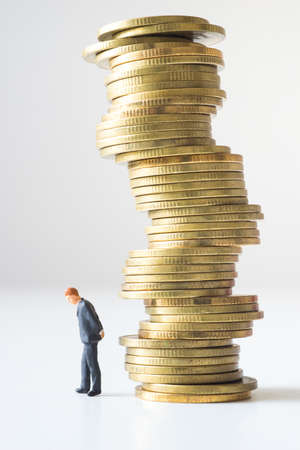 risky: Businessman standing under risky coin stack. Financial crisis concept.