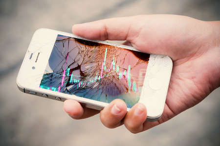 broken telephone: Hands holding broken mobile smartphone with stock graph overlay. Investment risk stock concept.