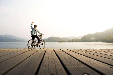 Jonge vrouw fietsen op de pier kijken natuurlijk meer met de vuist in de lucht.