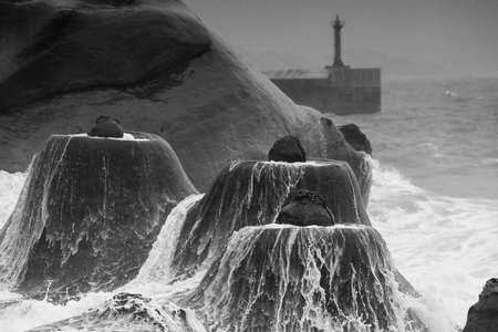 geologic: Candlestick rock formations against storm wave at Yehliu Coast Geologic Park.