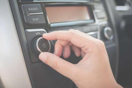 Hand tuning fm radio-knop in de auto panel. Retro beeld verwerkt.