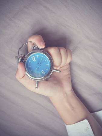 grabing: Hand grabing alarm clock on bed background Stock Photo