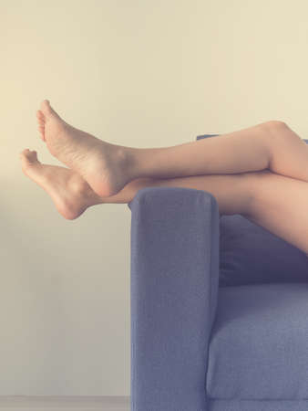 feminine beauty: Long woman legs on sofa. Stock Photo