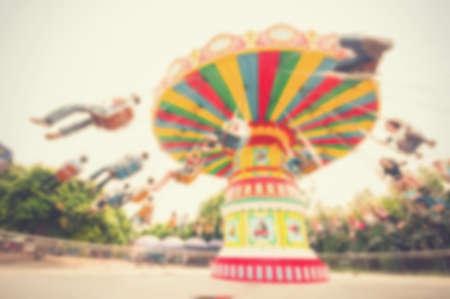 chain swing ride: Blur background image of people enjoy roller swings in amusement park.