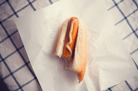 dog bite: Hot Dog bite left on paper Stock Photo