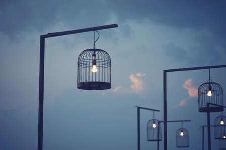 Cage à oiseaux décoré comme poste de lumière extérieure. Image vintage traitée.