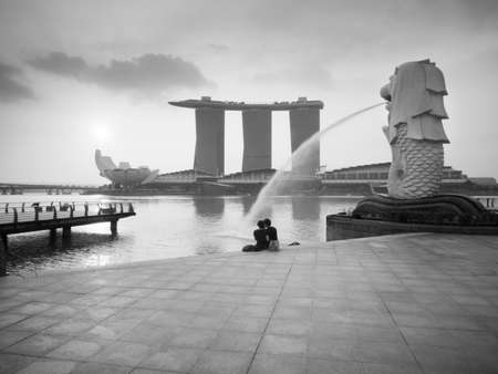 merlion: SINGAPORE - MARCH 10, 2013: Couple sitting relax in the morning at Merlion Park, Marina Bay. Merlion is a mythical creature with the head of a lion and the body of a fish is a symbol of Singapore. Editorial