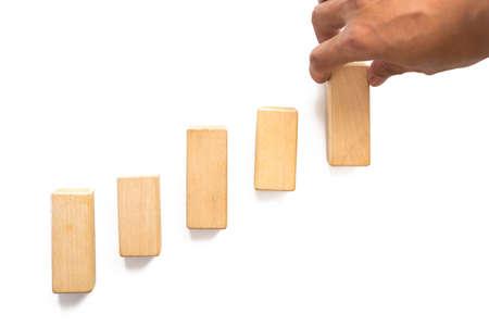 Hand uitstralende houtblok stapelen als opstaptrede. Bedrijfsconcept voor het proces van het de groeisucces.