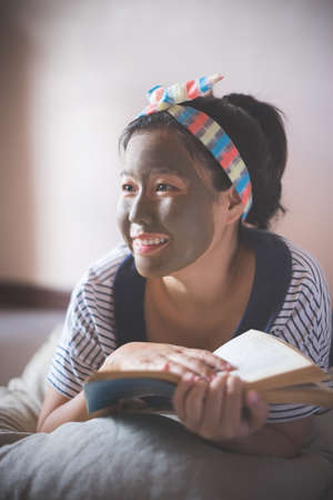 Pretty asian woman with relaxing smile doing mud facial masking at home D.I.Y. spa and reading a book. Stock Photo