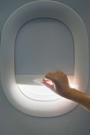 shut down: Hand pulling down aircraft window curtain while travelling on flight.
