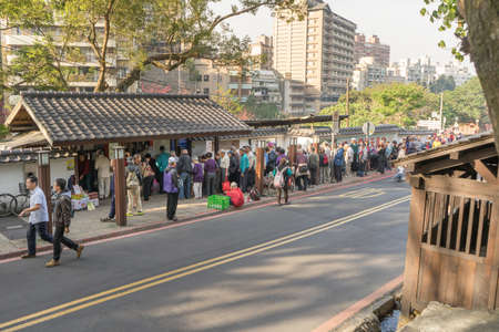 queueing: Beitou, Taiwan - March 05, 2016 : People queueing in front of public bath house at early morning. Many of the the baths are old style Japanese houses.